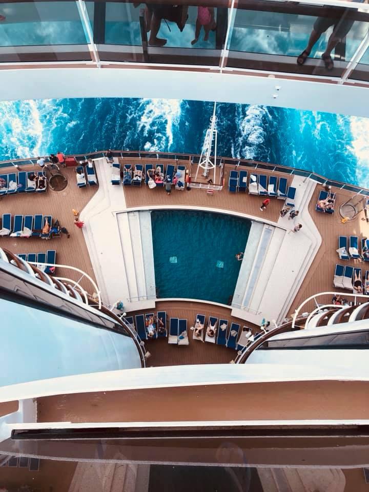 Uma foto tirada dentro do navio, mostrando a piscina e diversas cadeiras de descanso ao redor.
